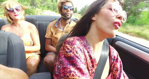 Beautiful young woman having fun driving her friends in convertible. Beautiful young dressed in boho style woman having fun driving her friends in convertible stock video footage