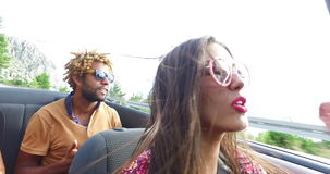 Beautiful young woman having fun driving her friends in convertible. Beautiful young woman with pink lipstick having fun driving her friends in convertible stock video footage