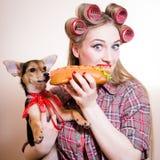 Beautiful young woman having fun eating hot-dog. Closeup portrait of beautiful young woman having fun eating hot-dog and holding little puppy Royalty Free Stock Image