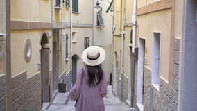 Beautiful young woman having fun during holidays in Cinque Terre. Young caucasian tourist walking at the old street in stock video