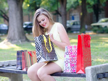 Beautiful young woman having fun in the park after shopping Stock Photo