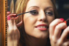 Beautiful young woman having fun while putting make up in front Stock Photography