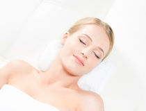 Beautiful young woman having leisure lying in a mat in spa Royalty Free Stock Photos