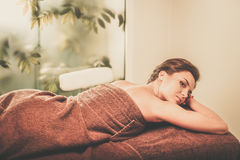 Beautiful young woman having massage in a spa salon. Stock Photos