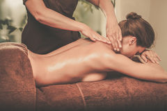 Beautiful young woman having massage in a spa salon. Royalty Free Stock Images