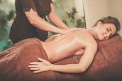 Beautiful young woman having massage in a spa salon. Stock Photography