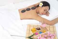 Beautiful young woman having massage with stones in spa salon..Beauty woman relaxing in spa. Hot stone massage pebbles on back royalty free stock photo