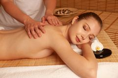 Beautiful young woman having a massage treatment in spa salon - wellness.  royalty free stock image