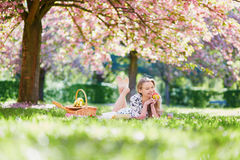 Beautiful young woman having picnic in blooming spring park Stock Photos