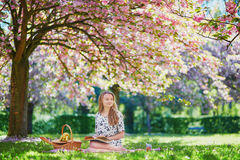Beautiful young woman having picnic in blooming spring park Royalty Free Stock Image