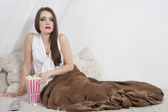 Beautiful young woman having popcorn while sitting in bed Stock Photo