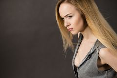Beautiful woman having serious face expression. Beautiful young woman having serious nervous face expression looking scary. Dark background Stock Photography
