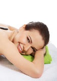 Beautiful young woman having stone massage. Royalty Free Stock Photography
