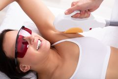 Woman Having Underarm Laser Hair Removal Treatment. Beautiful Young Woman Having Underarm Laser Hair Removal Treatment In Spa royalty free stock images