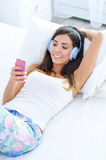 Beautiful young woman in headphones with cell phone in her hand Stock Photography