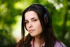 Beautiful young woman in headphones listening to music on the ba. Ckground of nature, close-up. Enjoy music, technology, audio books, lifestyle concept Stock Photo