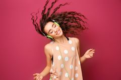 Beautiful young woman in headphones listening to music. And dancing on color background Royalty Free Stock Photography