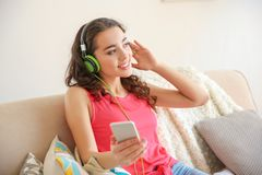 Beautiful young woman in headphones listening to music. At home Stock Images