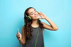 Beautiful young woman in headphones listening to music. On light background Royalty Free Stock Photography