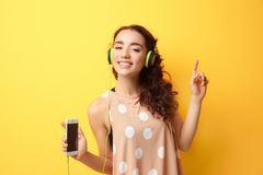 Beautiful young woman in headphones listening to music. On yellow background Stock Photos