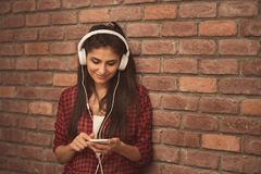 Beautiful young woman in headphones listening to music on brick background.  Stock Photo