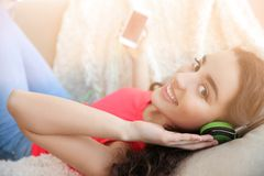 Beautiful young woman in headphones listening to music. At home Stock Photo