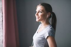 Beautiful young woman in headphones listening to music at home royalty free stock photo