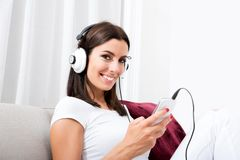 Beautiful young woman in headphones listening to music Royalty Free Stock Photography