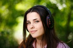 Beautiful young woman in headphones listening to music and smili. Ng on the background of nature, close-up. Enjoy music, technology, audio books, lifestyle Royalty Free Stock Image
