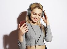 Beautiful blond  woman in headphones listening to music on white Stock Images