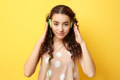 Beautiful young woman in headphones listening to music. On yellow background Royalty Free Stock Photos