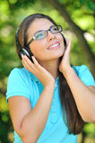 Beautiful young woman with headphones outdoors. Enjoying music Royalty Free Stock Images