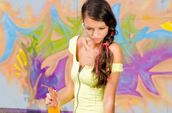 Beautiful young woman with headphones relaxing and listening to music while drinking orange juice. Royalty Free Stock Images