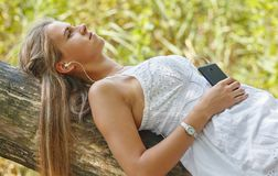 Beautiful young woman with headphones relaxing on nature. She is listening to music using a phone, chill out and leisure concept Royalty Free Stock Photos