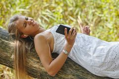 Beautiful young woman with headphones relaxing on nature. She is listening to music using a phone, chill out and leisure concept Royalty Free Stock Photography