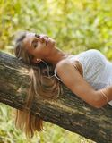 Beautiful young woman with headphones relaxing on nature. She is listening to music using a phone, chill out and leisure concept Stock Image