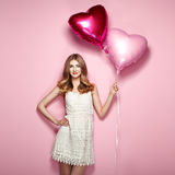 Beautiful young woman with heart shape air balloon. On color background. Woman on Valentine`s Day. Symbol of love Stock Photography