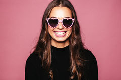Beautiful young woman with heart shaped sunglasses. Portrait of beautiful young woman with heart shaped sunglasses and smiling against pink background. Caucasian Stock Image