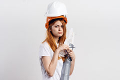 Beautiful young woman in a helmet holding blueprints on white isolated background, engineer.  Stock Photography