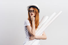 Beautiful young woman in a helmet holding blueprints on white isolated background, engineer, building.  Royalty Free Stock Photo