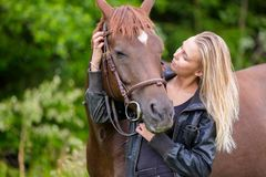 Young woman with her arabian horse standing in the field Stock Photos
