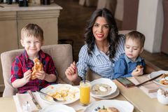 Beautiful young woman with her baby sons. Light breakfast near window in a cafe. Croissants, omelet, coffee and many. Beautiful young women with her baby sons stock image