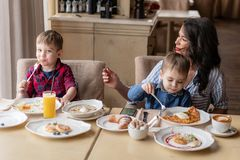 Beautiful young woman with her baby sons. Light breakfast near window in a cafe. Croissants, omelet, coffee and many. Beautiful young women with her baby sons royalty free stock image