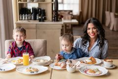 Beautiful young woman with her baby sons. Light breakfast near window in a cafe. Croissants, omelet, coffee and many. Beautiful young women with her baby sons stock images