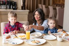 Beautiful young woman with her baby sons. Light breakfast near window in a cafe. Croissants, omelet, coffee and many. Beautiful young women with her baby sons royalty free stock photo