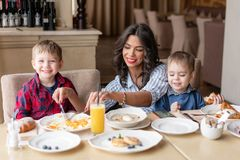 Beautiful young woman with her baby sons. Light breakfast near window in a cafe. Croissants, omelet, coffee and many. Beautiful young women with her baby sons stock photography