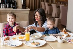 Beautiful young woman with her baby sons. Light breakfast near window in a cafe. Croissants, omelet, coffee and many. Beautiful young women with her baby sons royalty free stock photography