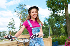 Beautiful young woman with her bicycle at the park. Attractive young woman standing with her bicycle at the local park smiling to the camera happily copyspace royalty free stock photos