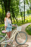 Beautiful young woman with her bicycle standing on a footpath in Royalty Free Stock Image