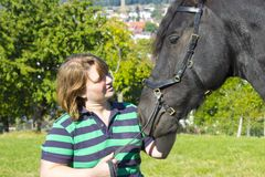 Beautiful young woman with her black horse Stock Photos